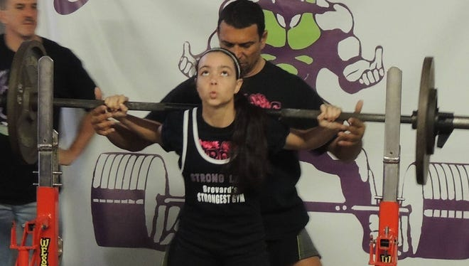 """Megan Lee, 14, broke the record in the Teenage Division, and won the """"Best Lifter"""" award at the Raw United Federation Power Weight lifting Florida State Championship last weekend."""
