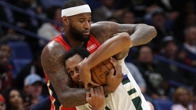 The Pelicans' DeMarcus Cousins wraps up  John Henson in a battle for the ball Wednesday night in New Orleans.