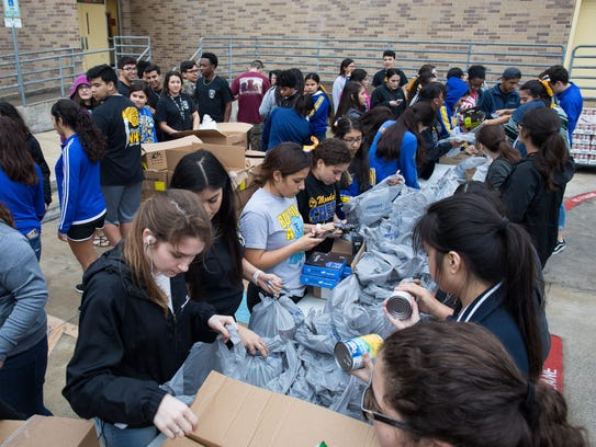 Students package canned goods from the Coastal Bend