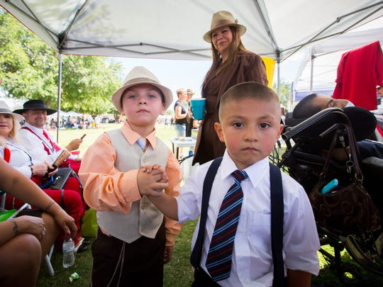 """Zachary Patino, 4, left, and Demonathan Portillo, 3, shake hands at Klein Park, during the first Zoot Suit Pachanga, June 4, 2016. The pachanga, which in Spanish is defined as a party or """"bash"""", was organized to celebrate the culture of the Mesquite Historic District."""