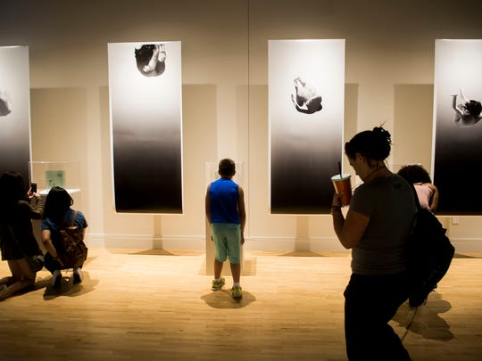"""ArtPrize goers take in """"Swing,"""" by Dana Freeman at the Kendell College of Art and Design in Grand Rapids on Sept. 24, 2016."""