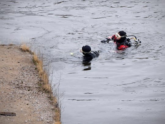 Divers search an area of the Mississippi River Thursday,