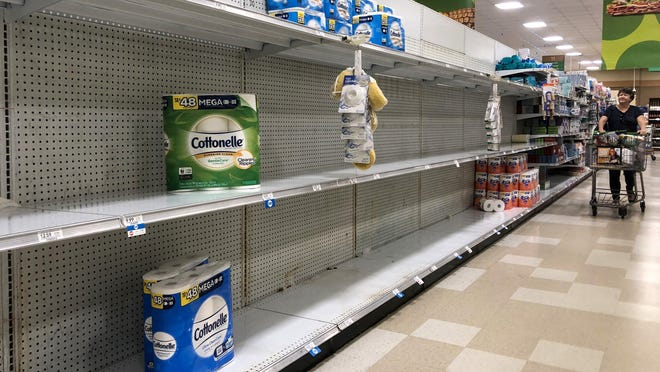Annie Bowman pushes her cart down an aisle looking for toilet paper at a Publix store Tuesday in West Palm Beach. Supplies have dwindled in the wave of coronavirus panic buying not just in Palm Beach County but around the world.