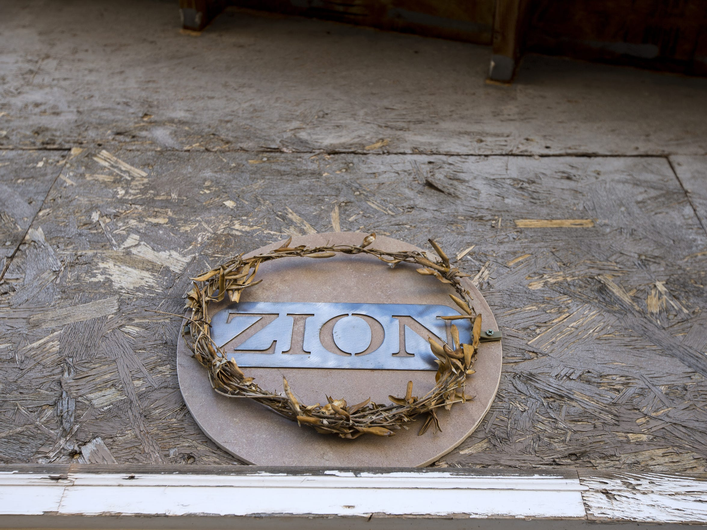 """A sign that reads """"ZION"""" hangs above the front door"""