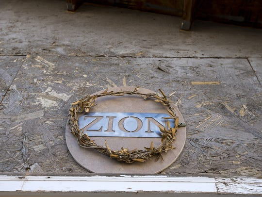 "A sign that reads ""ZION"" hangs above the front door"