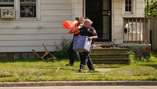 Ingham County Animal Control officers leave a house in the 1700 block of West Saginaw early Thursday evening, July 27, 2017, with boxes and bags.  Members of the Michigan State University Police department were also on scene.