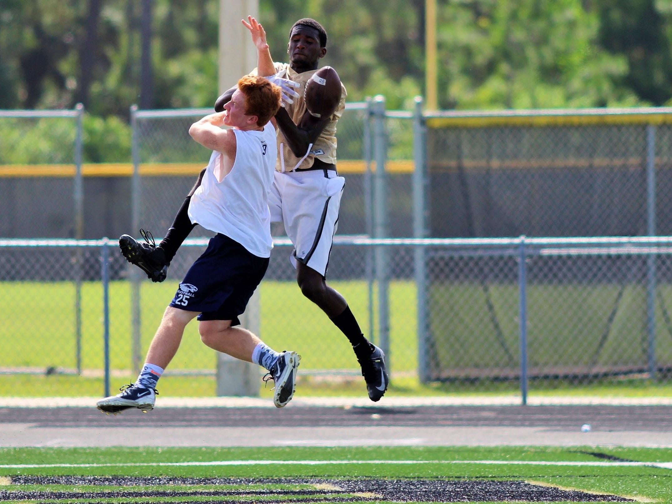 Golden Gate wide receiver Patrick Volcy goes up for a pass with a Naples defensive back during a 7-on-7 game at Golden Gate High School on July 8, 2015.
