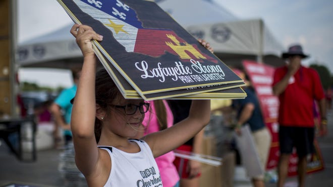 """Meredith Cantrelle, 8, holds a handful of """"Lafayette Strong"""" signs."""