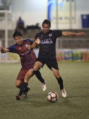 FC Familia's Donald Weakley gets past Bank of Guam Strykers I's Eddie Huang to the ball during a Week 5 match of the Budweiser Soccer League Saturday night at the Guam Football Association National Training Center. The Strykers I won 7-0.