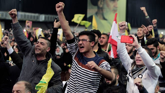 Hezbollah supporters raise their hands in salute as their leader Sheikh Hassan Nasrallah speaks via video in the southern suburb of Beirut on Jan. 30, 2015.