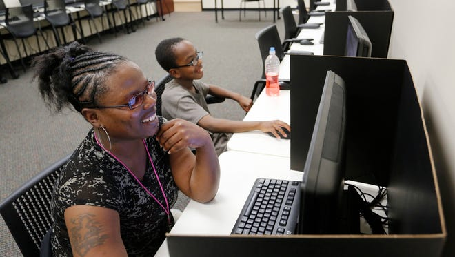 With her son Derez, 9, seated at her side, Debbie De Ramus works on an economics tutorial for one of her classes Tuesday, May 27, 2014, at the Excel Center located inside the Howarth Center, 615 N. 18th Street in Lafayette. Pat Fassnacht, Regional Director for Excel Center, said De Ramus is one of the few students who always arrives early for classes and then remains afterward to continue learning.
