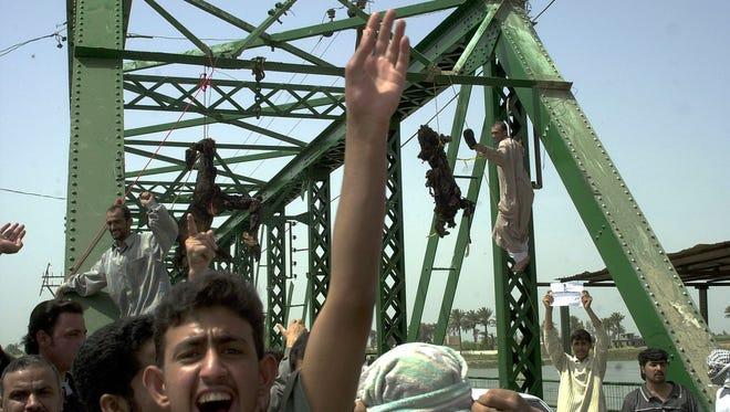 Iraqis in Fallujah celebrate after killing four U.S. contractors in March 2004.