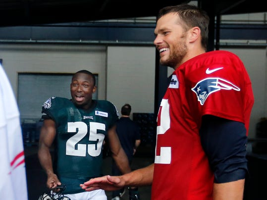 New England Patriots quarterback Tom Brady, right, and Philadelphia Eagles running back LeSean McCoy (25) chat after a joint NFL football training camp practice in Foxborough, Mass., Wednesday, Aug. 13, 2014. (AP Photo/Elise Amendola)