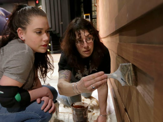 """Scenic artist Nerissa Eichinger (right) works with UW-Milwaukee sophomore Alexia Stessl in painting a set Tuesday. The Mainstage Theatre has been rebuilt and upgraded after a fire gutted it last April. Members of the stage crew were preparing for the upcoming performance of """"9 to 5: The Musical."""""""