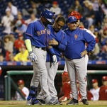 The New York Mets' Yoenis Cespedes, left, is assisted after being hit by a pitch from the Philadelphia Phillies' Justin De Fratus during the third inning Wednesday in Philadelphia.