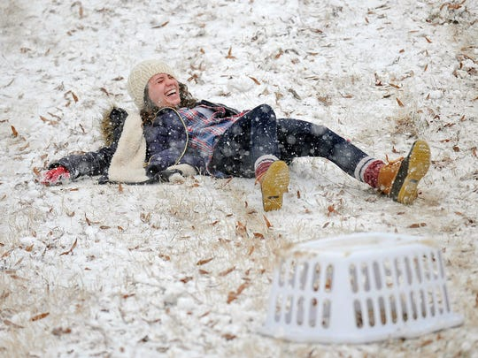 This 2015 photo shows an Ole Miss student laughing after sliding down a hill on the campus in Oxford, Miss.
