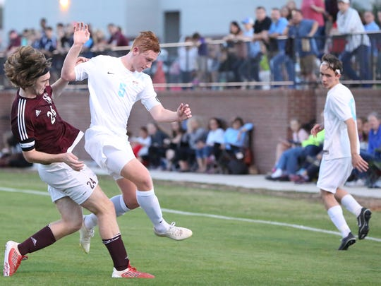 Sacred Heart 's Sean Graham (24) clears the ball from the feet of USJ's Jack Edwards on Tuesday.