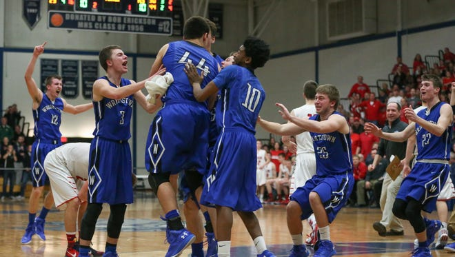 Wrightstown players run off the bench to congratulate Nathan Beining (44) on his game-winning shot to beat Valders on Thursday in Menasha.