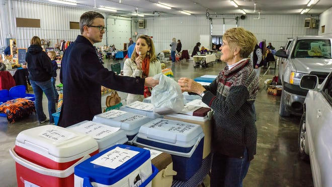 Brian Rennekamp and Haley Pittman of Iowa City shop with Lois Pavelka of Pavelka's Point Meats at the Winter Farmers Market Sunday at the Johnson County Fairgrounds.