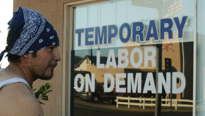 "Unemployed father of two, Michael Lopez (L) waits for work outside a temporary labor office in the southern Californian town of El Centro, a town of 50,000 people where 30.4 percent of the work-age population are without employment, on October 28, 2010.  According to the latest data 13 US cities and towns -- including nine in California -- have a jobless rate of over 15 percent. The two ""recession capitals,"" as American media have dubbed them, are El Centro -- 365 km southeast of Los Angeles -- and the neighbouring town of Yuma in Arizona, where 27.2 percent of people are out of work. Both are in traditional farming regions whose economy has always depended on Mexican seasonal workers who come to work legally in the US due to special status enjoyed by residents of the border area. In El Centro, most unemployed people over 45 can expect to be without a job for up to two years; for those below 30 the wait is generally less than six months, but usually involves a string of temporary jobs in shops or fields.                     AFP PHOTO/Mark RALSTON (Photo credit should read MARK RALSTON/AFP/Getty Images)"