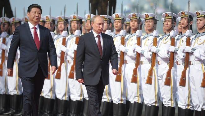 Russia's President Vladimir Putin and China's President Xi Jinping left, walk to open joint naval exercises in Shanghai, China, Tuesday.(AP Photo/RIA Novosti, Alexei Druzhinin, Presidential Press Service) ORG XMIT: MOSB114