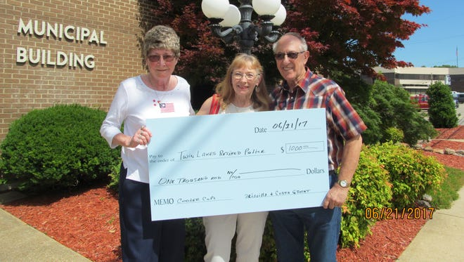 Mary Edwards (center) accepts a $1,000 donation for Law Enforcement Appreciation Day from Priscilla and Curtis Grant. Mr. Grant also presented a $100 donation from the Twin Lakes Base, United States Submarine Veterans Inc.