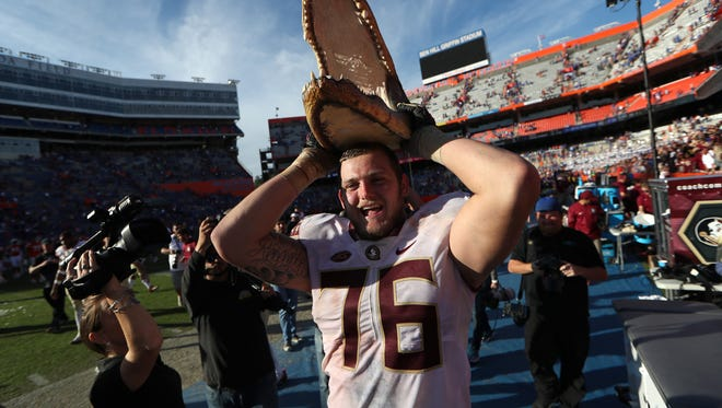 FSU's Rick Leonard holds up a gator hear in celebration of the Seminoles 38-22 win over Florida at Ben Hill Griffin Stadium in Gainesville on Saturday.