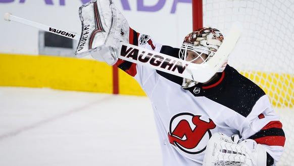 New Jersey Devils goalie Keith Kinkaid swats away the