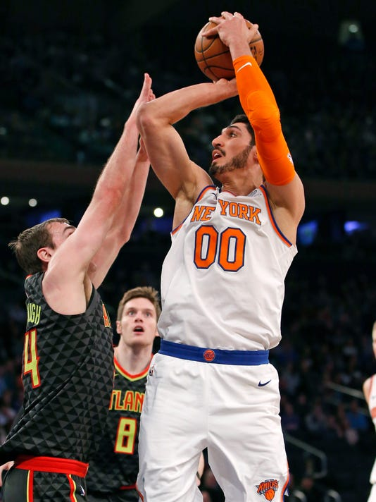 Atlanta Hawks forward Tyler Cavanaugh (34) defends as New York Knicks center Enes Kanter (00) prepares to shoot with Hawks forward Luke Babbitt (8) watching in the first half of an NBA basketball game at Madison Square Garden in New York, Sunday, Dec. 10, 2017. (AP Photo/Kathy Willens)