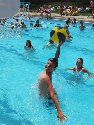 Nathan Ulanowski, 15, of Florence tries to dunk the beach ball into the pool side basket with his sister Briana, 17, cheering him on at the R.C. Durr YMCA in June 2008 in Burlington. The year the YMCA is launching an expansion and fundraising drive for the Burlington facility.