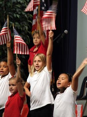 """A section of the Tommie Barfield Elementary School """"Morning Musicians"""" group sing joyously as they perform America - Land of the Free."""