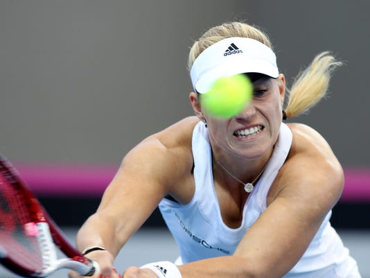 Angelique Kerber of Germany plays a shot in her match against Samantha Stosur of Australia during the Fed Cup semifinals between Australia and Germany in Brisbane, Australia, Sunday, April 20, 2014. (AP Photo/Tertius Pickard)
