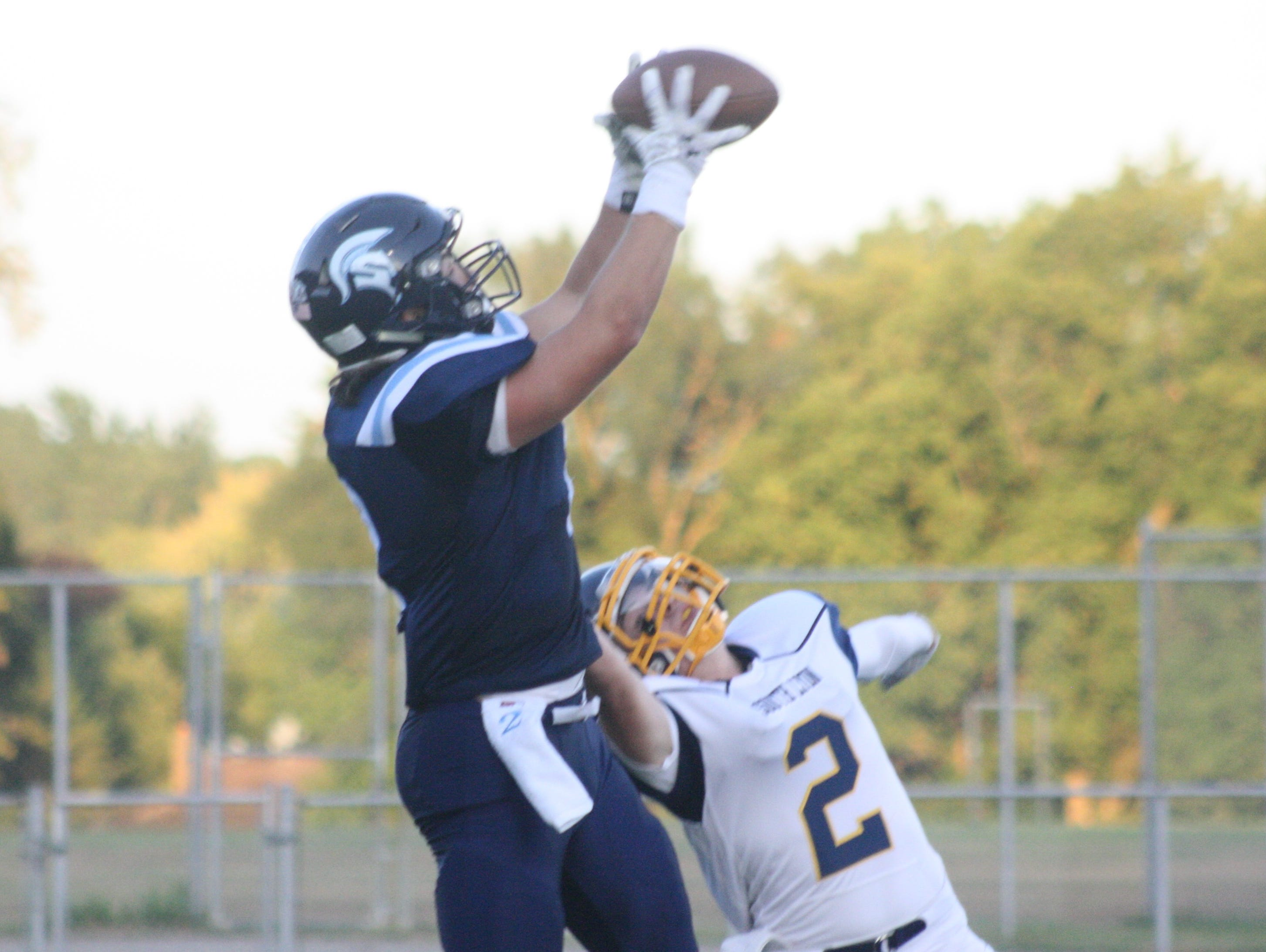 Livonia Stevenson's Austin Petries hauls in a touchdown pass from Chris Tanderys 20 seconds into Friday's 35-0 victory over South Lyon.