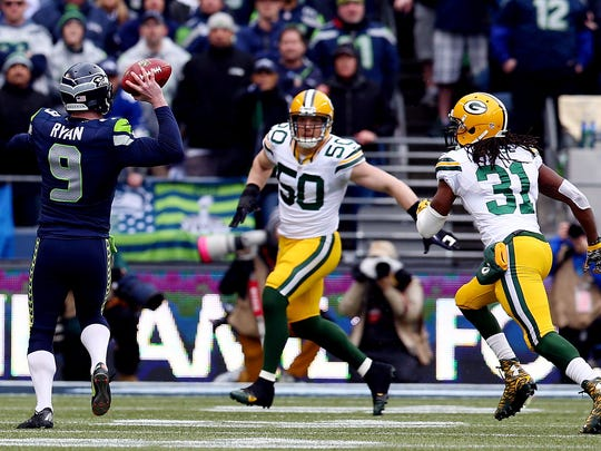 Seattle Seahawks holder Jon Ryan throws a 19-yard touchdown pass to Garry Gilliam against Green Bay Packers defenders A.J. Hawk (50) and Davon House (31) during the third quarter of Sunday's NFC championship game at CenturyLink Field in Seattle.
