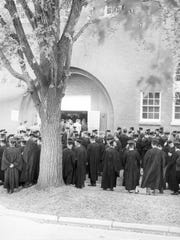 St. Michael's students gather in graduation regalia outside the North Campus Gym during the 1960s.