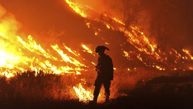 In this Aug. 3, 2015 file photo, CalFire firefighter Bo Santiago lights a backfire as the Rocky fire burns near Clearlake, Calif.