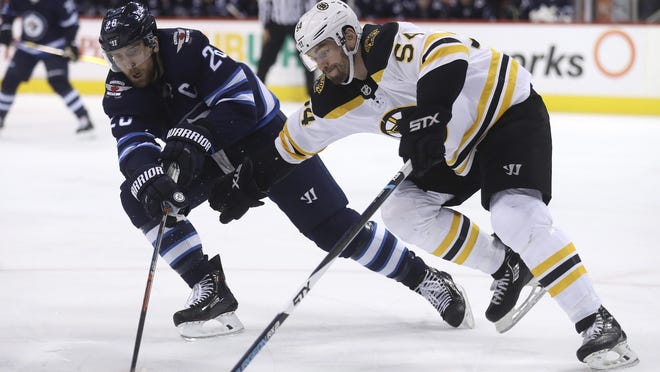 """""""It didn't matter what you did all summer,"""" said Winnipeg Jets captain Blake Wheeler, here at left battling the Bruins in March 2018, and who played for the U.S. in 2016. """"It was tough. And it's going to be tough in Edmonton."""""""