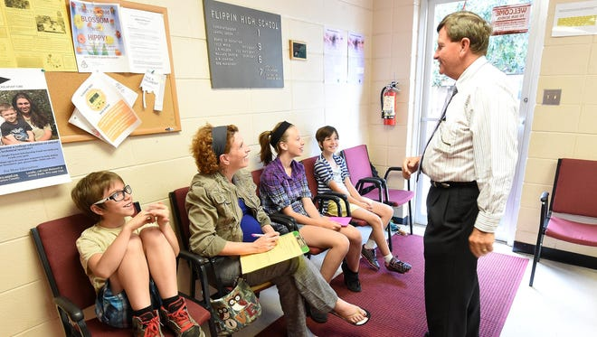 Dale Query, left, Flippin Schools superintendent, speaks with Christina Gleisner, second from left, and her kids on Tuesday. Gleisner was enrolling Taven, 10, Tasmine, 12, and Teagan, 9, for classes when school begins at Flippin on Monday.