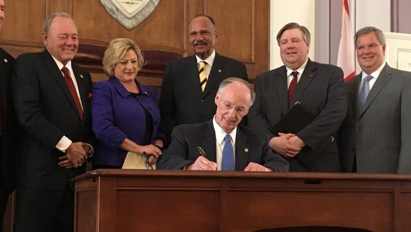 Gov. Robert Bentley signs an order on Tuesday, February