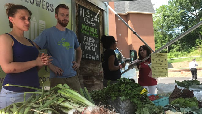 Lauren Sprich, a Montclair State University intern with City Green, left, and Liam Geraghty, the nonprofit's farm crew leader, at City Green's mobile farm stand in Belleville on June 13, 2017.