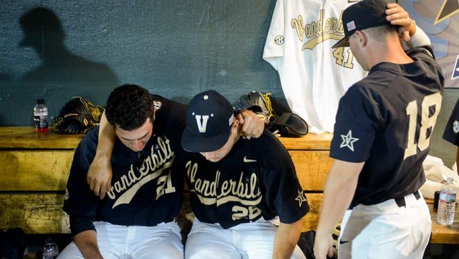 Vanderbilt pitcher John Kilichowski (21), pitcher Matt Ruppenthal (28) and outfielder Nolan Rogers (18) console one another next to pitcher Donny Everett's jersey after their 9-8 loss to Washington on Saturday night.