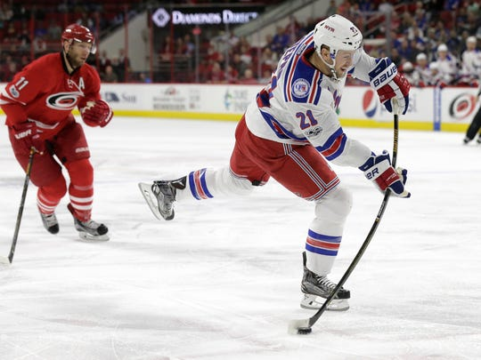 In this March 9, 2017, file photo, New York Rangers' Derek Stepan (21) shoots as Carolina Hurricanes' Jordan Staal (11) watches during the first period of an NHL hockey game in Raleigh, N.C.