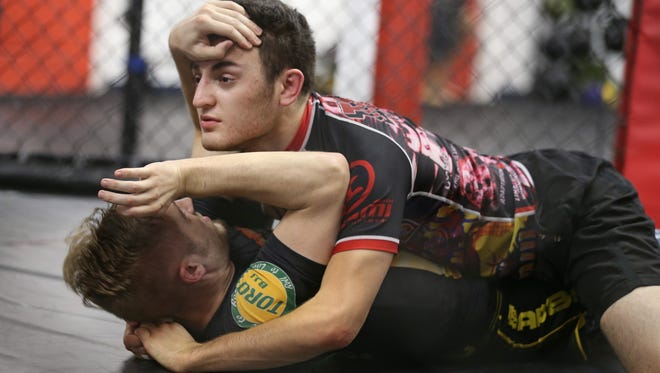 """Cody Lockley, Williamson, bottom, stars the """"jaws of life"""" move on Ted Hancock, Rochester, to get out from his bottom position while practicing inside the cage."""