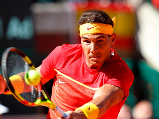 FILE - In this Sunday April 8, 2018 file photo, Spain's Rafael Nadal returns the ball to Germany's Alexander Zverev during a World Group quarterfinal Davis Cup tennis match between Spain and Germany at the bullring in Valencia, Spain. Rafael Nadal is wary of saying he's fully recovered from a troublesome right thigh injury as he defends his Monte Carlo Masters title. The top-ranked Spaniard only recently returned to action at the Davis Cup, after a recurrence of the injury forced him out of the Mexico Open and then Masters tournaments at Indian Wells and Miami last month. (AP Photo/Alberto Saiz, File)