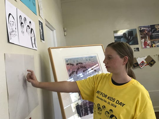 Margaret Ryan, 12, shows some of her drawings on display