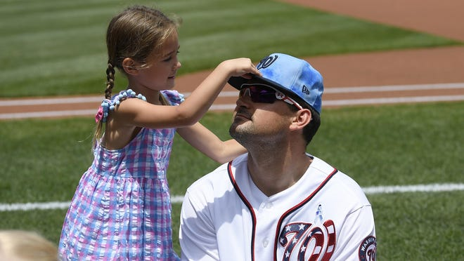 "The Nationals' Ryan Zimmerman has his cap adjusted by his daughter Mackenzie before a game against the Diamondbacks in Washington last season. Zimmerman is uncertain if he'll play this season for several reasons: His mother is ""super high risk"" given her age and multiple sclerosis, and his wife Heather recently gave birth to their third child."