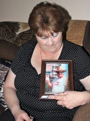 Rhonda Askew looks at a framed photo of her late husband Dave.