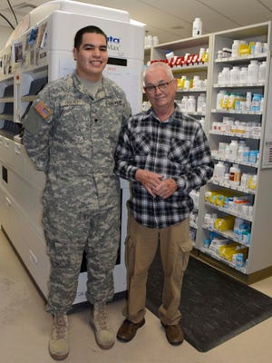 Pharmacist Brian Blacklock, right, and Pharmacy Technician Spc. Pablo Chavez, left, pose for a picture inside the White Sands Missile Range McAfee Health Clinic Pharmacy during National Pharmacy Week.