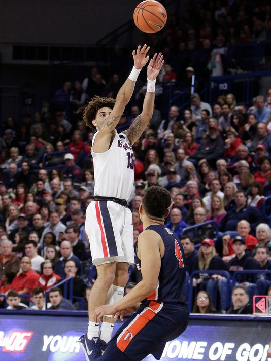 Gonzaga guard Josh Perkins, left, shoots over Pepperdine guard Colbey Ross during the first half of an NCAA college basketball game in Spokane, Wash., Saturday, Feb. 17, 2018. (AP Photo/Young Kwak)
