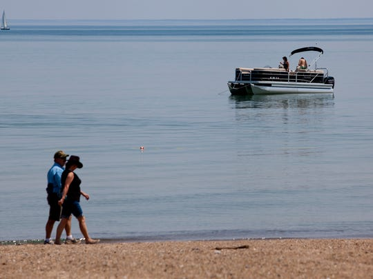 People walk along the beach and anchor their boats Thursday at Lakeside Park in Port Huron.